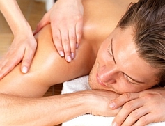 Happy handsome man getting a back massage by female hands. Enjoying a holiday at the beauty spa.